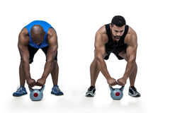 Strong friends lifting kettlebells together Royalty Free Stock Images