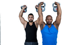 Strong friends lifting kettlebells together Stock Photo