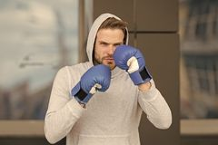 Strong and full of energy. Sportsman concentrated training boxing gloves. Athlete concentrated face with sport gloves. Practice fighting skills urban background stock photo