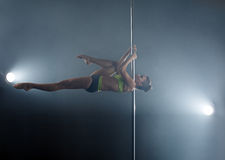 Strong girl dancing on pole in rays of spotlights Royalty Free Stock Photo