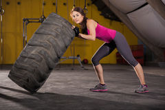 Strong girl flipping a tire Royalty Free Stock Image