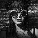 Strong girl with glasses and cap standing in the shower Stock Images