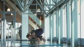 Strong girl make a Bakasana Crane Pose Crow Pose. Woman practicing yoga in a studio indoors. Meditation. Spiritual practice. The spiritual mentor. Bakasana ( stock footage