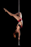 Strong girl show gymnastic exercise in pole dance Royalty Free Stock Photos