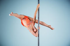 The strong and graceful young girl performing acrobatic exercises on pylon Stock Image