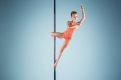 The strong and graceful young girl performing acrobatic exercises on pylon. The strong and graceful sports young girl performing acrobatic exercises on pylon on Stock Image