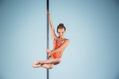 The strong and graceful young girl performing acrobatic exercises on pylon. The strong and graceful sports young girl performing acrobatic exercises on pylon on Royalty Free Stock Images