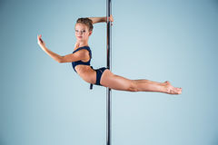The strong and graceful young girl performing acrobatic exercises on pylon. The strong and graceful sports young girl performing acrobatic exercises on pylon on Royalty Free Stock Photos
