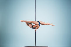 The strong and graceful young girl performing acrobatic exercises on pylon. The strong and graceful sports young girl performing acrobatic exercises on pylon on Royalty Free Stock Photo