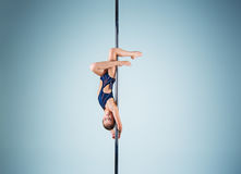 The strong and graceful young girl performing acrobatic exercises on pylon. The strong and graceful sports young girl performing acrobatic exercises on pylon on Stock Photo