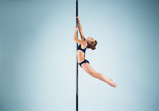 The strong and graceful young girl performing acrobatic exercises on pylon. The strong and graceful sports young girl performing acrobatic exercises on pylon on Royalty Free Stock Photography