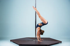 The strong and graceful young girl performing acrobatic exercises on pylon. The strong and graceful sports young girl performing acrobatic exercises on pylon on Stock Photos