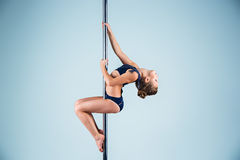The strong and graceful young girl performing acrobatic exercises on pylon. The strong and graceful sports young girl performing acrobatic exercises on pylon on Royalty Free Stock Image