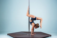 The strong and graceful young girl performing acrobatic exercises on pylon. The strong and graceful sports young girl performing acrobatic exercises on pylon on Stock Photography