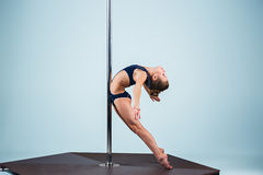 The strong and graceful young girl performing acrobatic exercises on pylon. The strong and graceful sports young girl performing acrobatic exercises on pylon on Stock Images