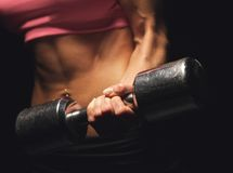 Strong Grip. Strong woman's hand lifting a dumbbell Stock Images