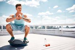 Serious man is squatting on BOSU platform on high balcony royalty free stock image