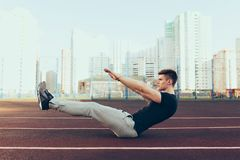 Strong guy with a good body in the morning on stadium. He wears sport clothes, doing exercise. He looks tense.  royalty free stock photography