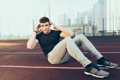 Strong guy with a good body training in the morning on stadium. He wears sport clothes, rocks press. He looks to the. Camera royalty free stock images