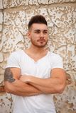 Strong guy with muscled arms. With an old wall of background royalty free stock image