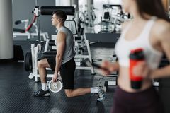 Strong guy sitting in a position, ready to do squats with his girlfriend standing nearby in gym.  royalty free stock photo