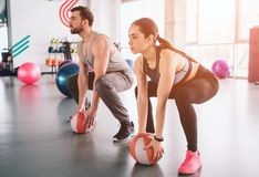 Strong guy and a slim girl are sitting in a position, ready to do squats. They have put their hands on balls ready to. Take them and hold it over their hands in stock images