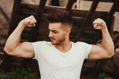 Strong guy with a tattoo on his arm outside. Strong guy with a tattoo on his arm in al old house stock image