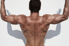 Strong and handsom. Male model posing in half body topless opposit white wall Stock Images