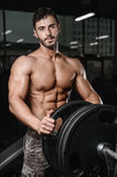 Strong and handsome athletic young man muscles abs and biceps. Strong and handsome athletic young man with muscles abs and biceps. Close-up of a power fitness royalty free stock image