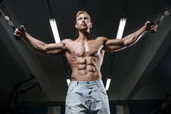Strong and handsome athletic young man muscles abs and biceps. Strong and handsome athletic young man with muscles abs and biceps. Close-up of a power fitness stock photo