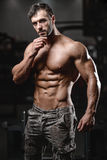 Strong and handsome athletic young man muscles abs and biceps Royalty Free Stock Image