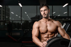 Strong and handsome athletic young man muscles abs and biceps. Strong and handsome athletic young man with muscles abs and biceps. Close-up of a power fitness Royalty Free Stock Photography