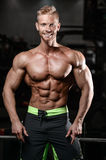 Strong and handsome athletic young man muscles abs and biceps Royalty Free Stock Photos