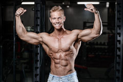 Strong and handsome athletic young man muscles abs and biceps fitness and bodybuilding. Strong and handsome athletic young man with muscles abs and biceps. Close Royalty Free Stock Photos
