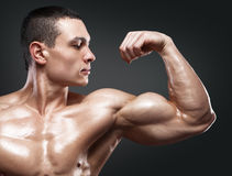Strong and handsome young bodybuilder demonstrate his muscles an. Close-up of a power fitness man's hand. Strong and handsome young bodybuilder demonstrate his Royalty Free Stock Image