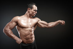 Strong and handsome young bodybuilder demonstrate his muscles an Royalty Free Stock Photo