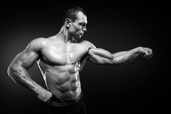 Strong and handsome young bodybuilder demonstrate his muscles an Royalty Free Stock Photography