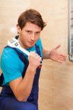 Strong handyman repairing radiator royalty free stock photo