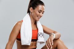 Strong happy cheerful young sports woman posing isolated indoors with towel looking at watch. Image of a beautiful strong happy cheerful young sports woman stock photos