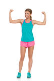 Strong Happy Woman Flexing Muscles. Smiling beautiful young woman in pink shorts, green tank top and sneakers standing and flexing muscles. Full length studio Royalty Free Stock Photo