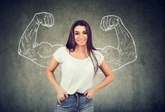 Strong happy young woman flexing her muscles. On gray background royalty free stock photo
