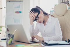Strong headache. Tired sick business lady lawyer with strong mig. Raine grimace. She is wearing the formalwear, sitting at the office, touching her forehead Royalty Free Stock Photo