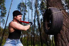 Strong healthy adult ripped man with big muscles hitting car tyr. E with big hammer. Outdoors workout, sports, power fitness, willpower, endurance exercises Royalty Free Stock Images