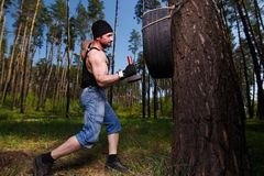 Strong healthy adult ripped man with big muscles hitting car tyr. E with two hammers. Outdoors workout, sports, power fitness, willpower, endurance exercises Stock Photos