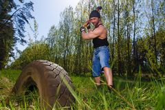 Strong healthy adult ripped man with big muscles hitting car tyr. E with big hammer. Outdoors workout, sports, power fitness, willpower, endurance exercises Stock Images