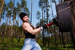 Strong healthy adult ripped man with big muscles hitting car tyr. E with big hammer. Outdoors workout, sports, power fitness, willpower, endurance exercises Stock Photography