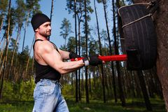 Strong healthy adult ripped man with big muscles hitting car tyr. E with big hammer. Outdoors workout, sports, power fitness, willpower, endurance exercises Stock Image