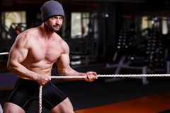 Strong healthy adult ripped man with big muscles tug of war topl. Strong ripped adult man with perfect abs, shoulders, biceps, triceps and chest. Bodybuilder tug royalty free stock photo