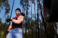 Strong healthy adult ripped man with big muscles working out wit. H big hammer and car tyre outdoors. Sports, power fitness, willpower, endurance exercises Stock Photography