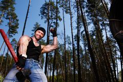 Strong healthy cheerful adult ripped man with big muscles workin. G out with big hammer and car tyre outdoors. Sports, power fitness, willpower, endurance Royalty Free Stock Photo